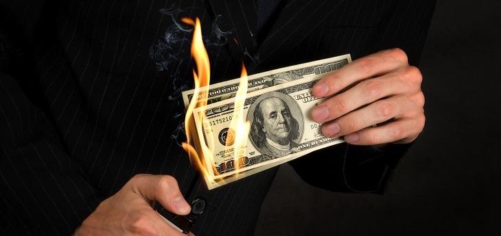 Businessman burning money in his hands