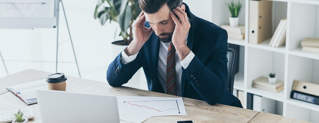 Man looking at chart and holding his head