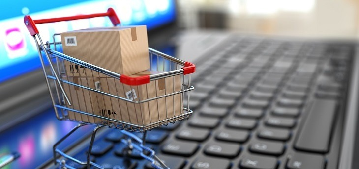Shopping cart with cardboard boxes on a laptop.